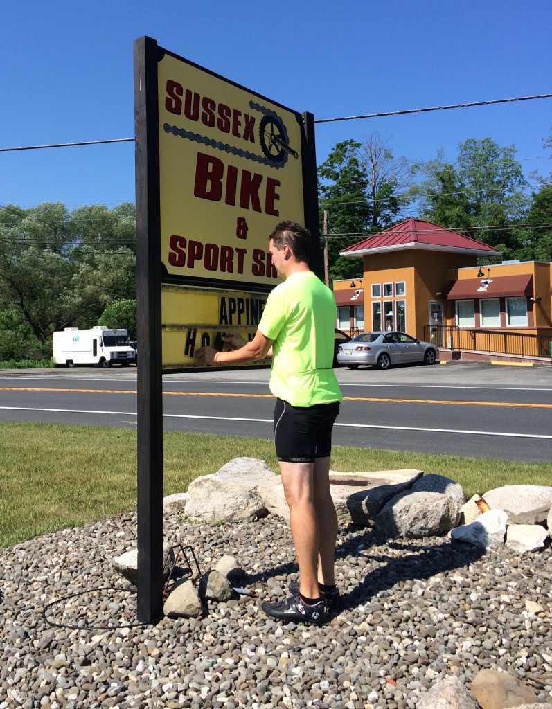 """No matter what it is that has to do with bikes, Ron's happy to fix it. Here he's straightening out the sign at Sussex Bike & Sport. """"Happiness On Two Wheels"""""""